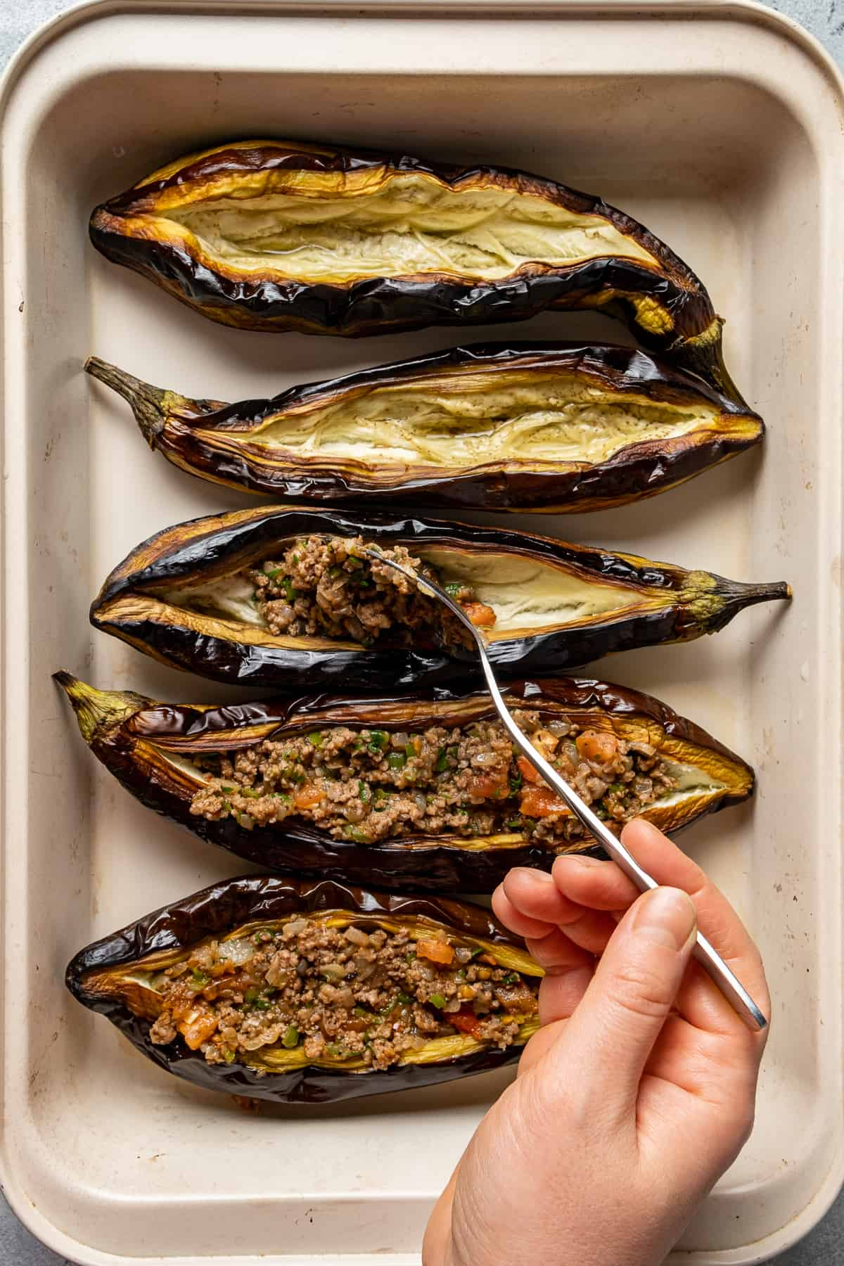 A hand stuffing the roasted whole eggplants with ground beef filling with a spoon.