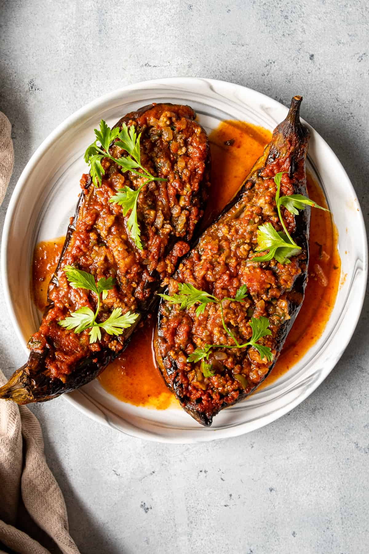 Turkish ground beef stuffed eggplants with tomato sauce garnished with parsley on a white plate.