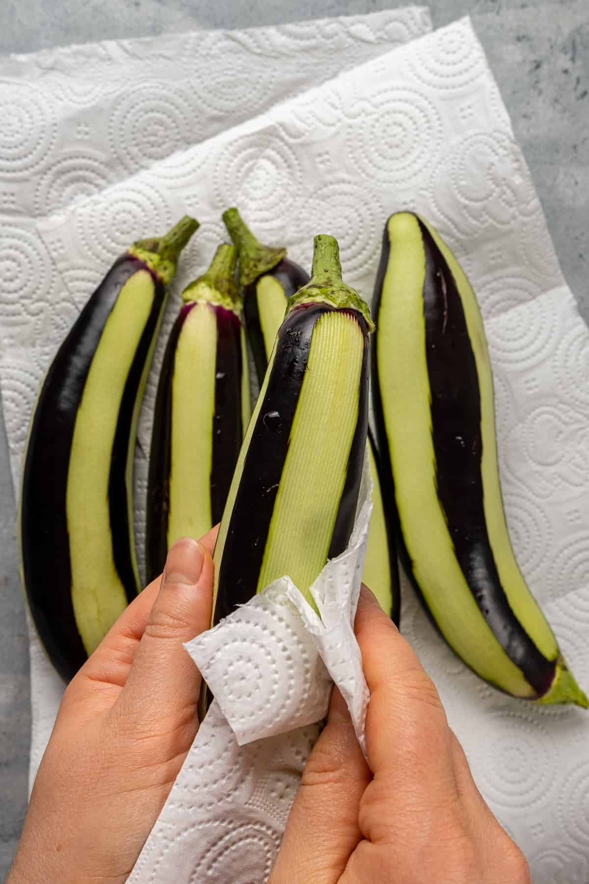 Hands drying peeled eggplants with a paper towel.