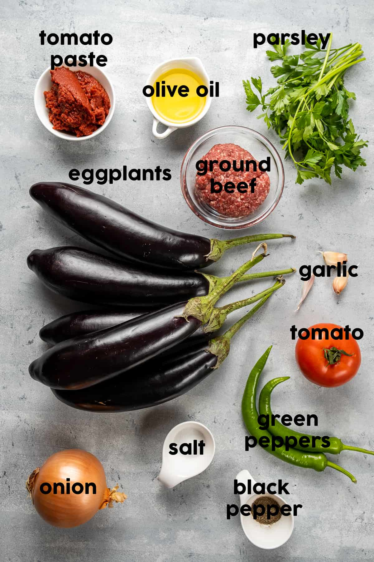 Eggplants, ground beef, tomato paste, olive oil, Turkish green peppers, a tomato, garlic cloves, onion, parsley on a grey background.