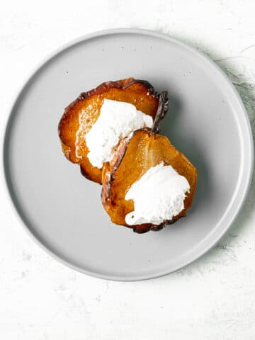 Two cinnamon baked pears topped with clotted cream on a round grey plate.