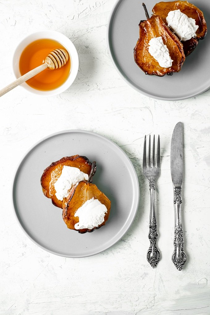 Roasted pears topped with clotted cream served on two grey round plates and honey in a bowl, a fork and a knife on the side.
