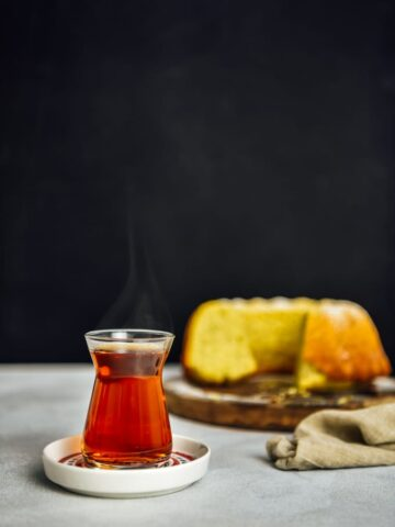 Hot Turkish tea served in a traditional Turkish tea glass on a tea plate photographed from front view with a dark background. Accompanied by a lemon cake.