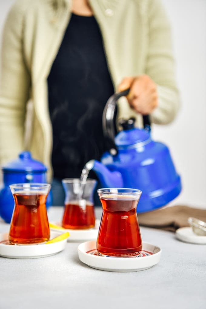 Woman serving Turkish tea in traditional tea glasses from a nostalgic teapot.