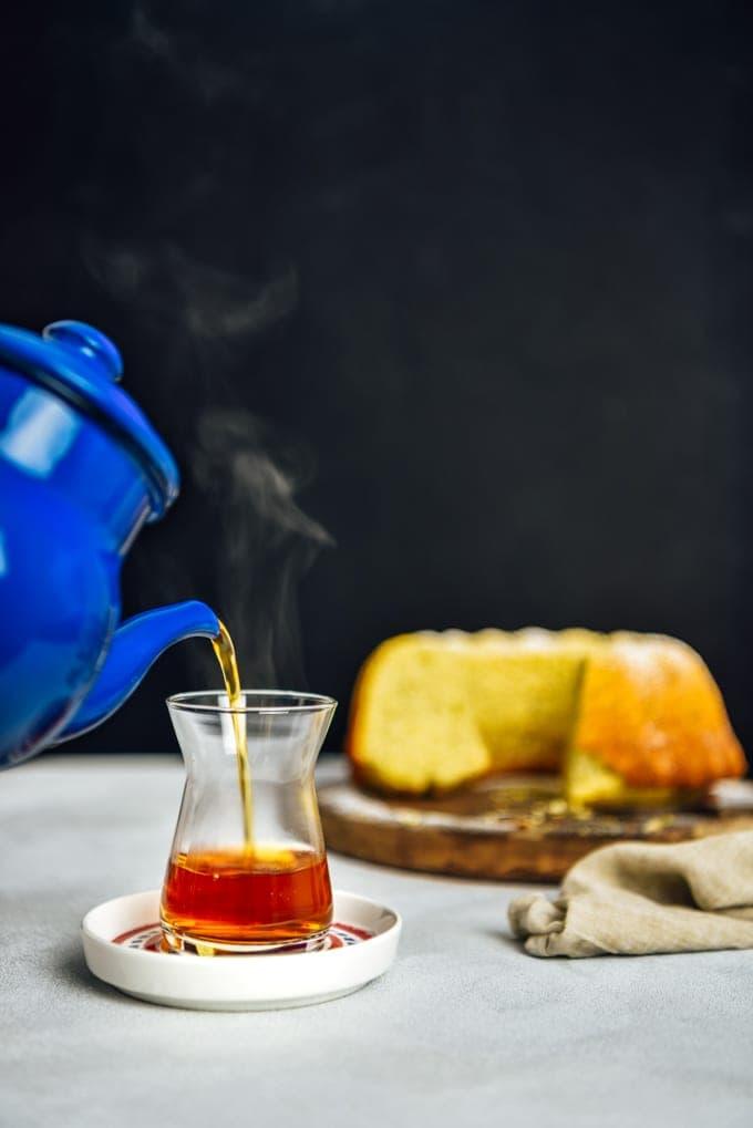 Pouring Turkish tea into a tea glass from a Turkish teapot. Accompanied by a lemon cake.