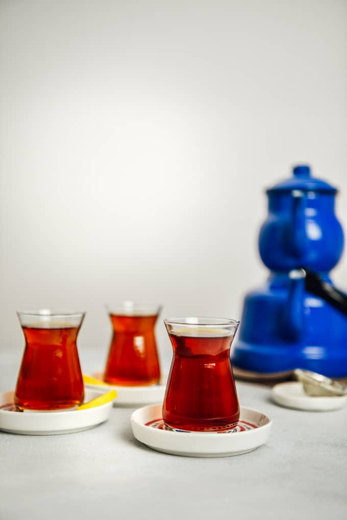 Turkish tea served in three Turkish tea glasses, thin lemon wedges on the side of two. Accompanied by a nostalgic blue tea pot set.
