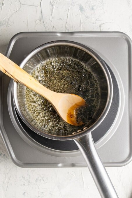 Mint butter sauce in a sauce pan and a wooden spoon in it.