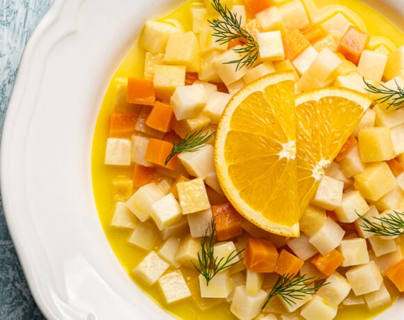Vegetarian celeriac recipe with carrots, quinces and citrus juice topped with orange wedges in a white round dish.