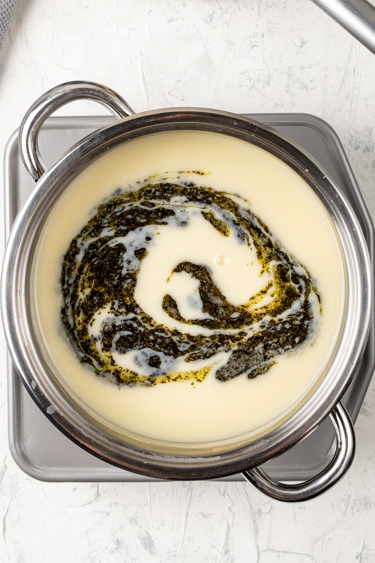 Turkish yayla corbasi topped with a butter mint sauce in a pot.