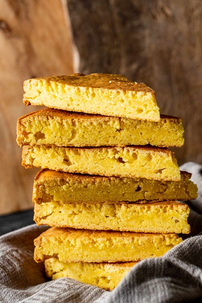 A stack of slices of cornbread made with hot water and wooden boards on the back.
