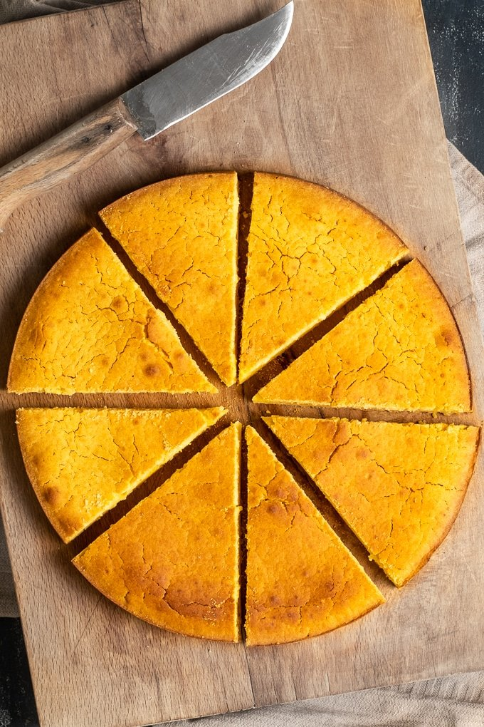 Hot water cornbread baked in a round pan, sliced on a wooden board and a knife on the side.