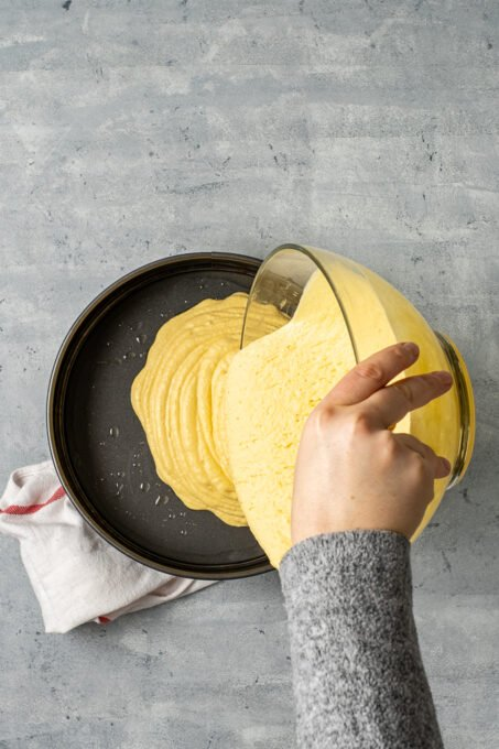 A woman's hand pouring cornbread batter into a round pan.