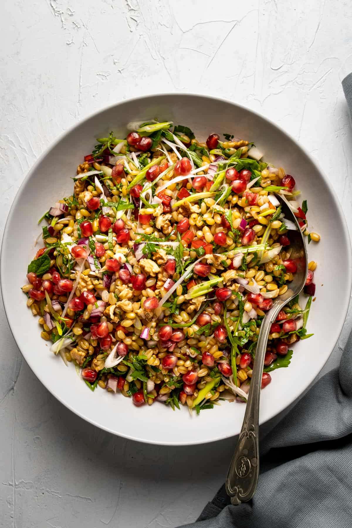 Wheat berries, herbs, onions and pomegranate arils combined in a white bowl and a spoon in it.