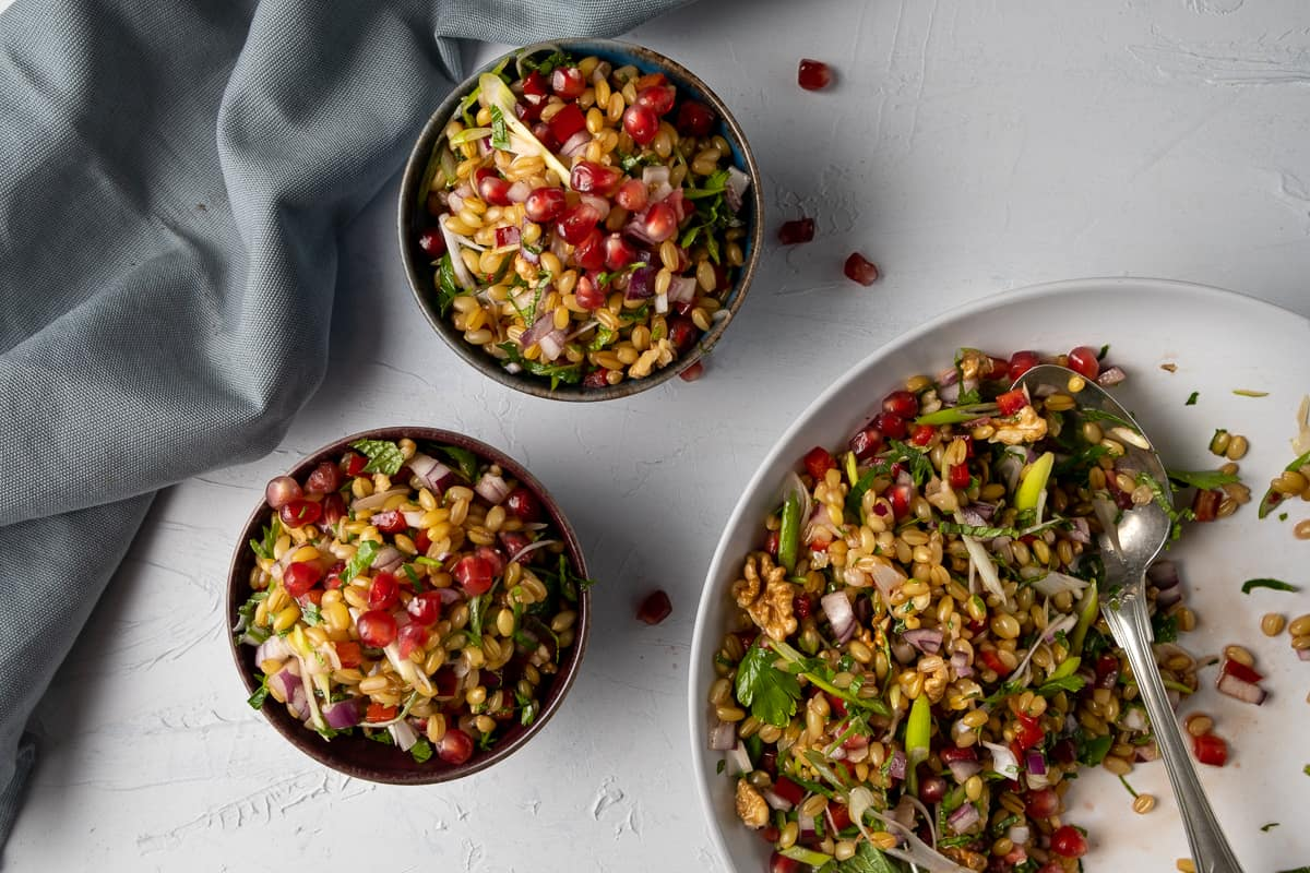 Salad with wheat berry grain and herbs in a white serving bowl and served in two black bowls and a grey napkin on the side.