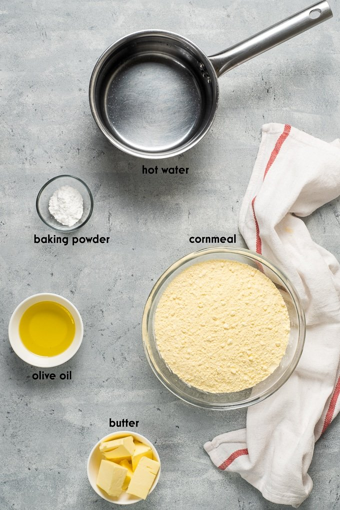 Ingredients for homemade cornbread on a grey background.