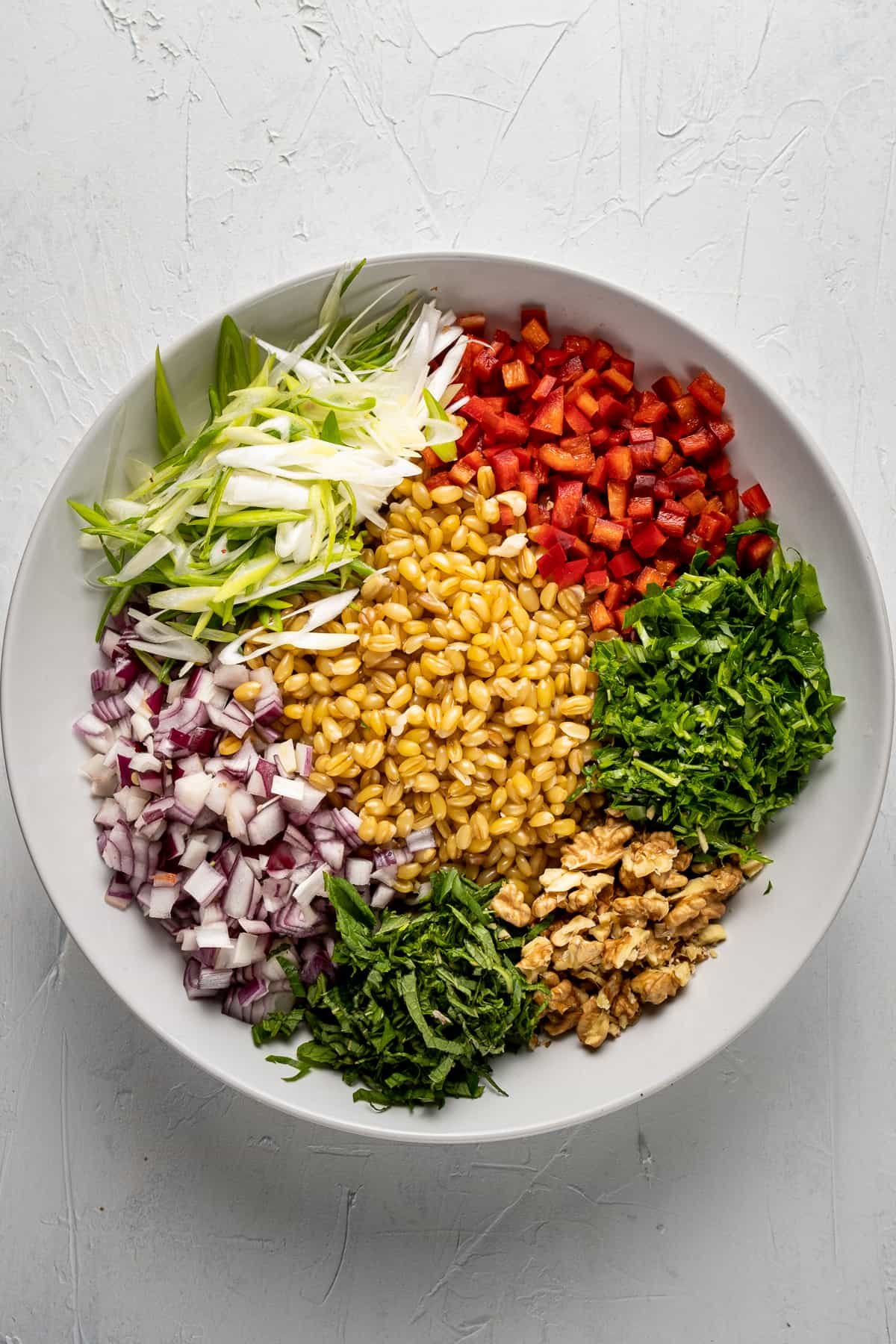 Cooked wheat berries, diced red onions and sweet red peppers, chopped herbs and walnuts arranged in a white bowl.