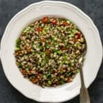 Black eyed pea salad with herbs, onions and sweet red pepper in a white dish and a spoon inside it.