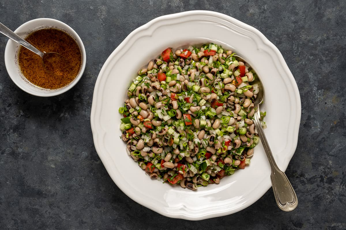 Black eyed pea salad in a white dish and lemon salad dressing in a small bowl next to it.
