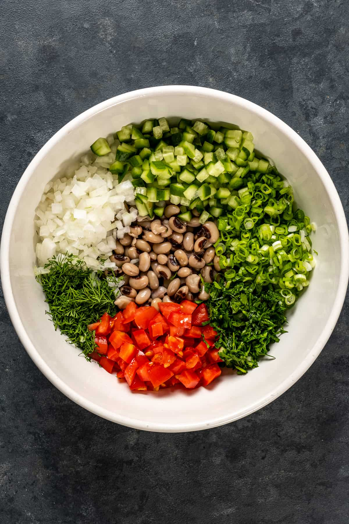 Finely chopped onion, green onion, herbs, tomato and cooked black eyed peas in a white bowl.
