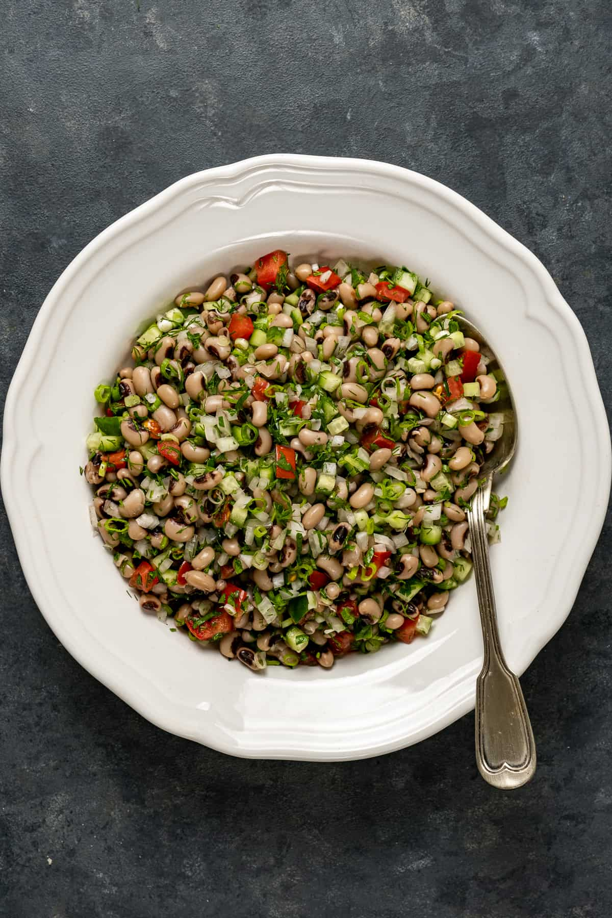 Black eyed pea salad in a white bowl with a spoon inside it.