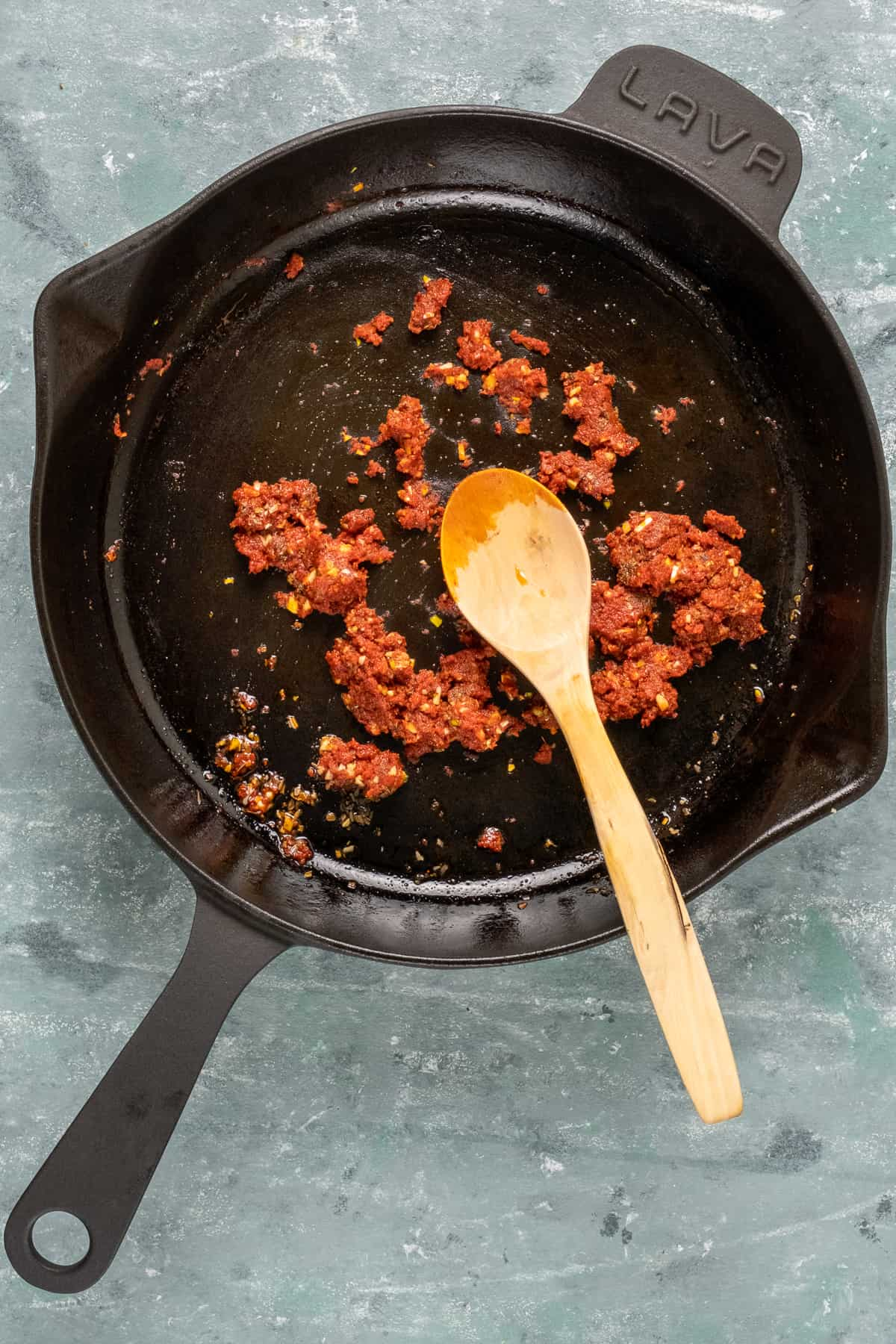 Spices and tomato paste cooking in a cast iron pan with a spoon inside it.
