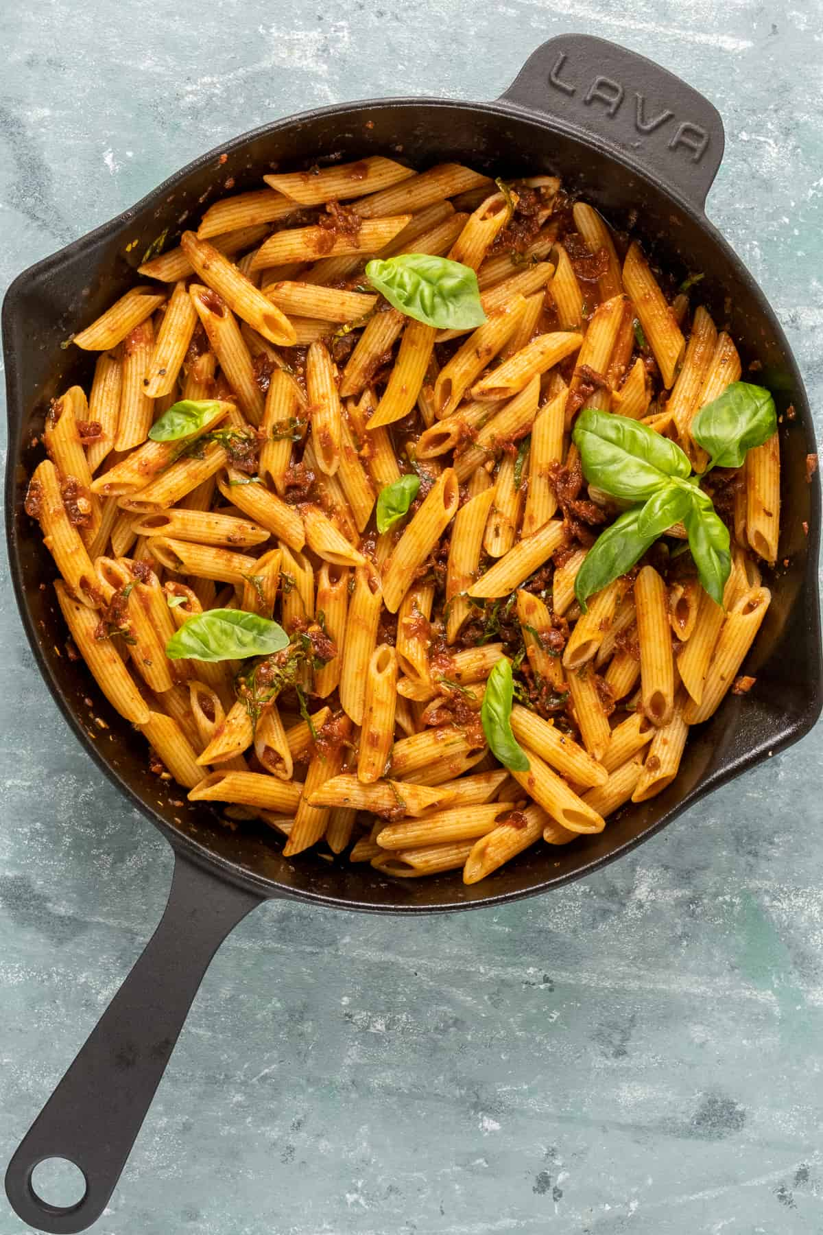 Pasta with sun-dried tomato sauce topped with basil leaves in a cast iron skillet.