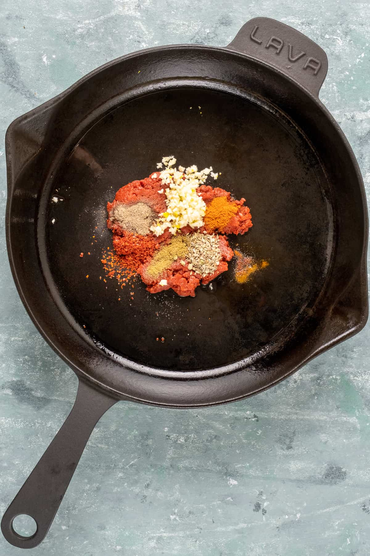 Spices, tomato paste and minced garlic in a cast iron skillet.
