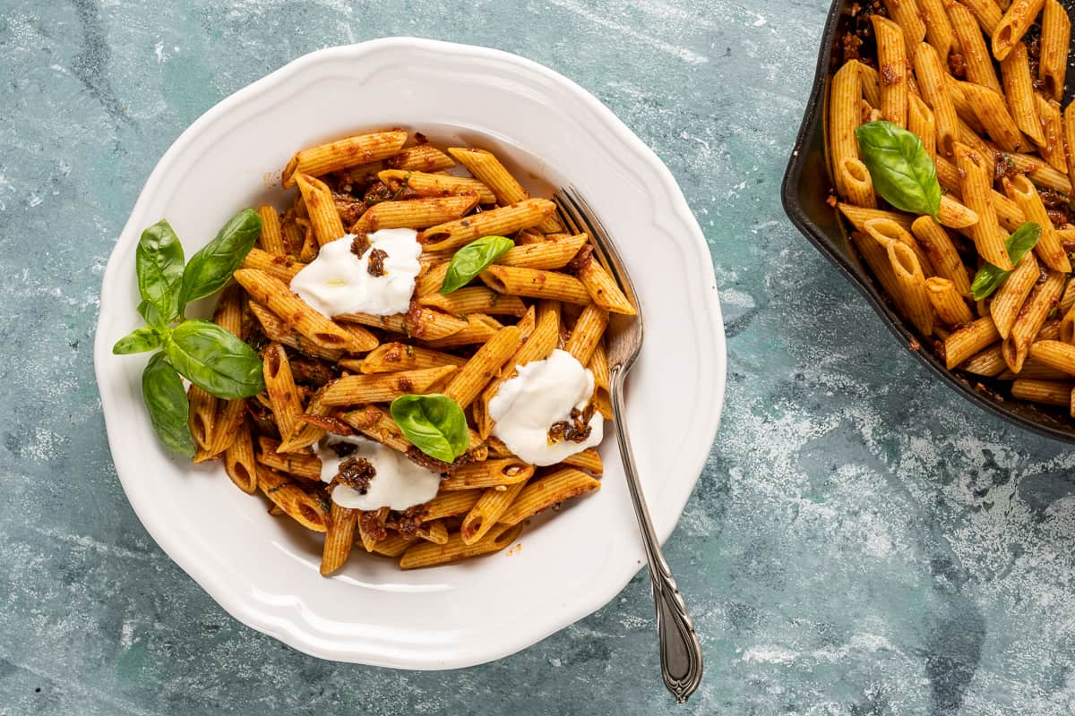Sun-dried tomato sauce pasta in a white bowl topped with yogurt and basil leaves and more pasta in a cast iron skillet on the side.