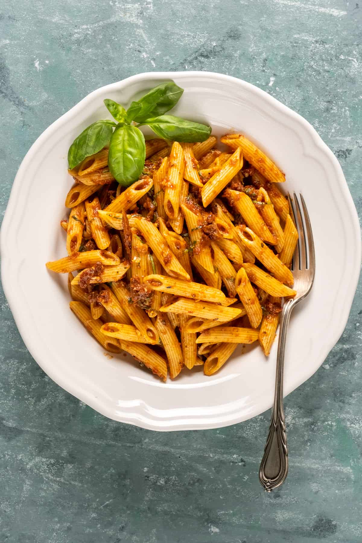 Pasta with a sun-dried tomato sauce in a white bowl topped with basil leaves and a fork inside.