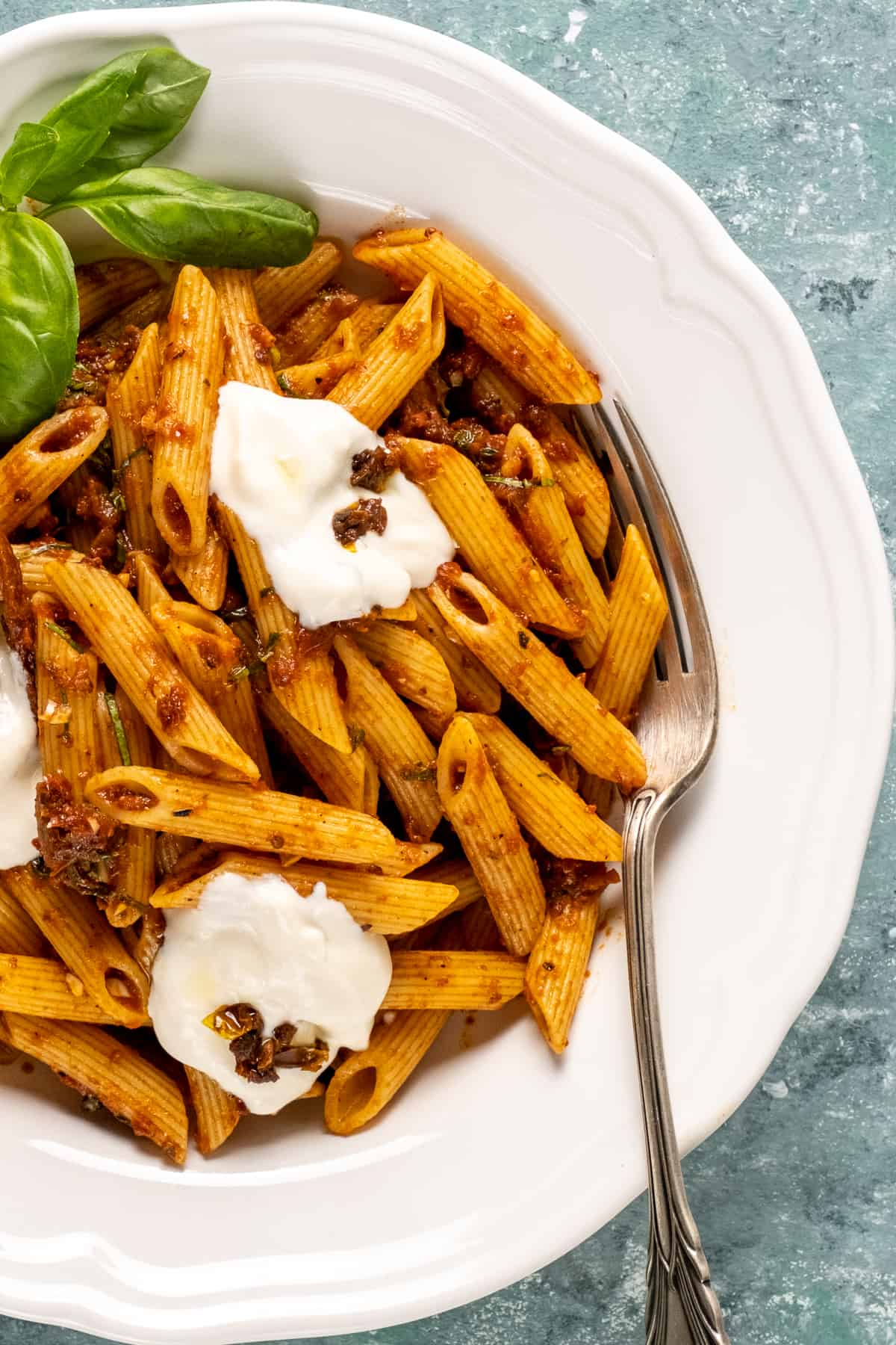 Sun-dried tomato pasta with basil and yogurt topping in a white bowl with a fork in it.