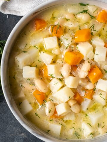 Celery root soup with apples, carrots and beans in a bowl on a dark background.