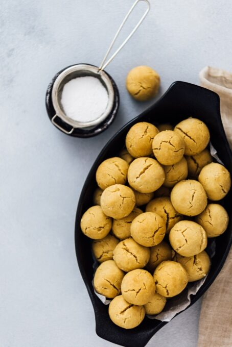 Mini tahini cookies in a black oval bowl photographed on a grey background.