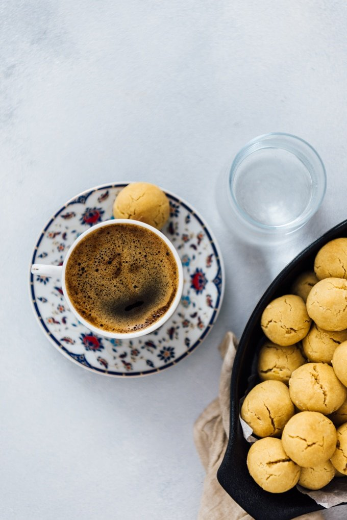 A cup of Turkish coffee is served with a tahini cookie on the side.