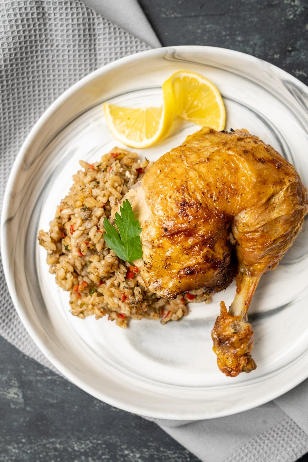 One portion rice stuffed chicken and a lemon slice on a white plate.