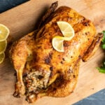 Rice stuffed whole chicken roasted in oven with a crispy golden skin photographed on a wooden board, lemon slices and a bunch of parsley on the side.