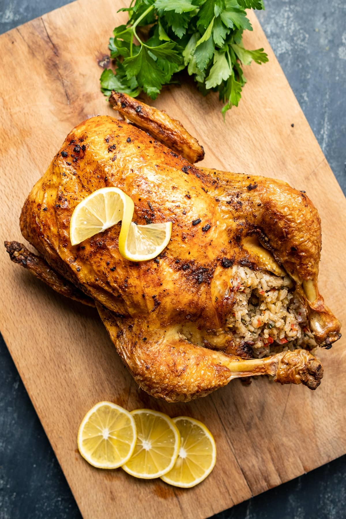 Roasted rice stuffed whole chicken on a wooden cutting board, lemon slices and a bunch of parsley on the side.