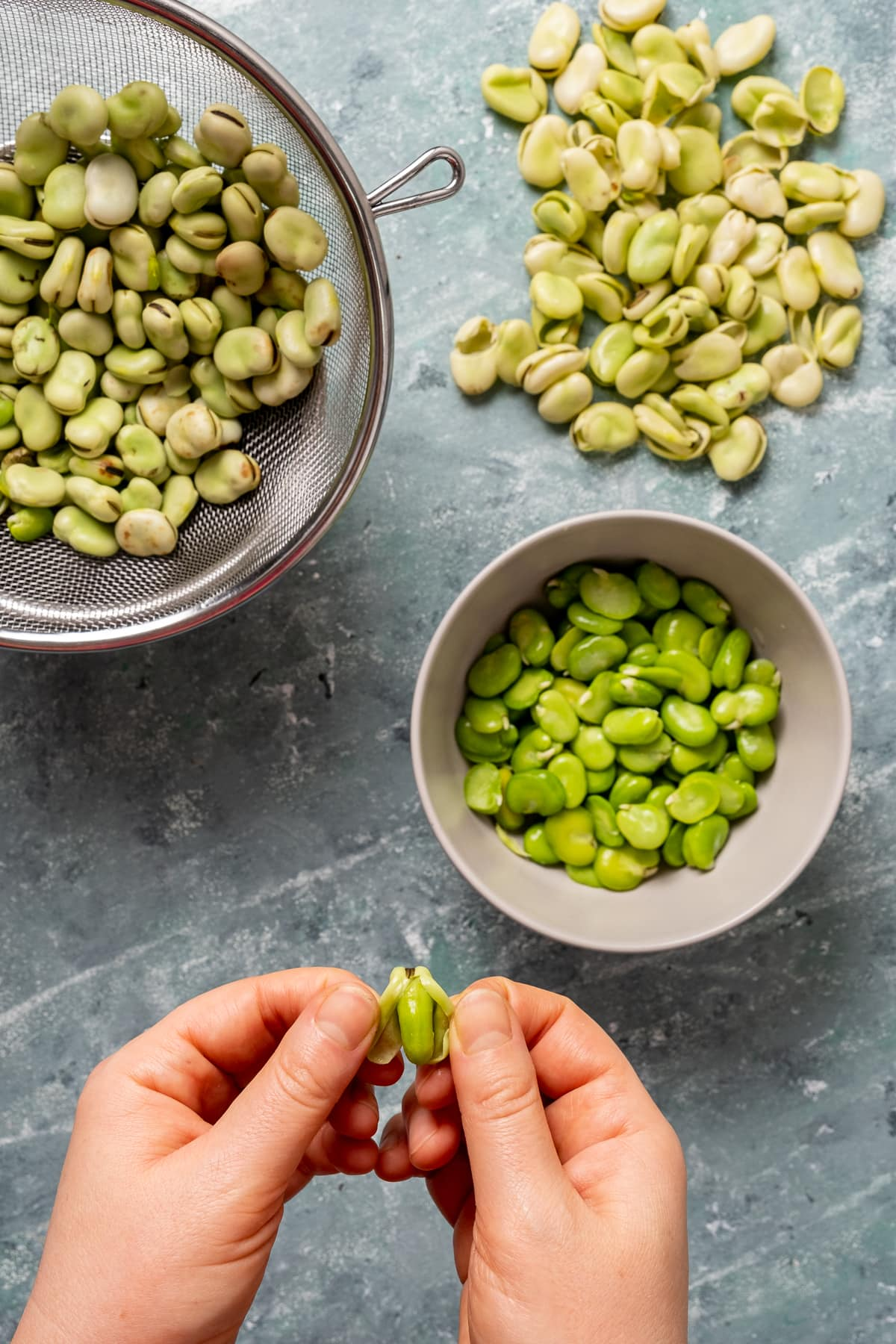 Hands peeling fresh fava beans removed from the pod, more shelled beans in a bowl, their skins on the ground and unpleed fava beans in a strainer.