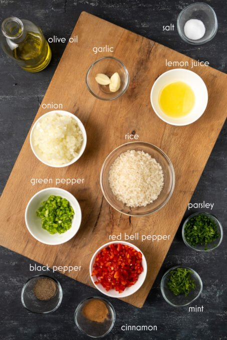Rice, garlic, chopped red and green bell peppers, herbs, spices on a wooden board and on a dark background.
