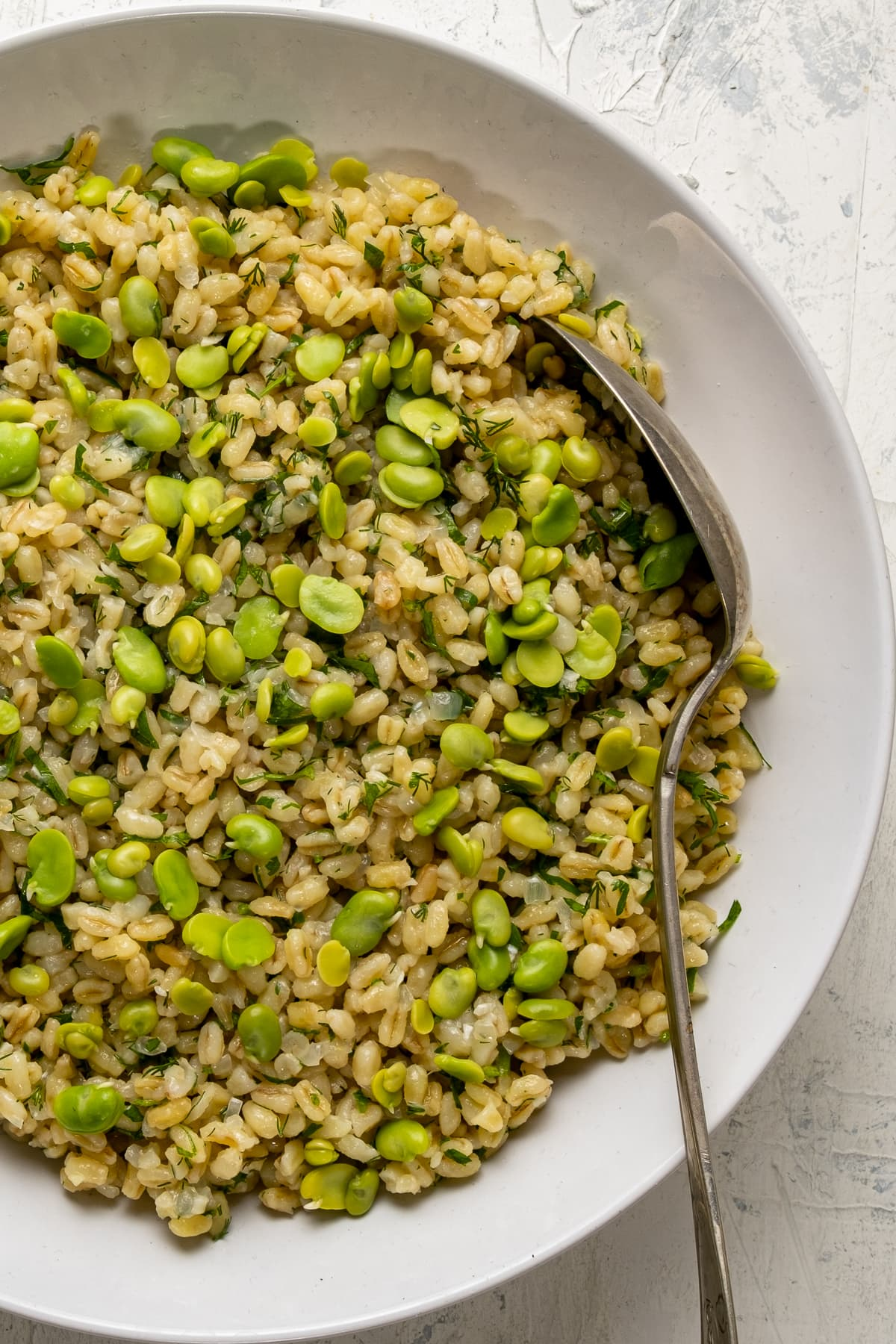 Bulgur pilaf with fava beans in a white bowl and a spoon inside it.