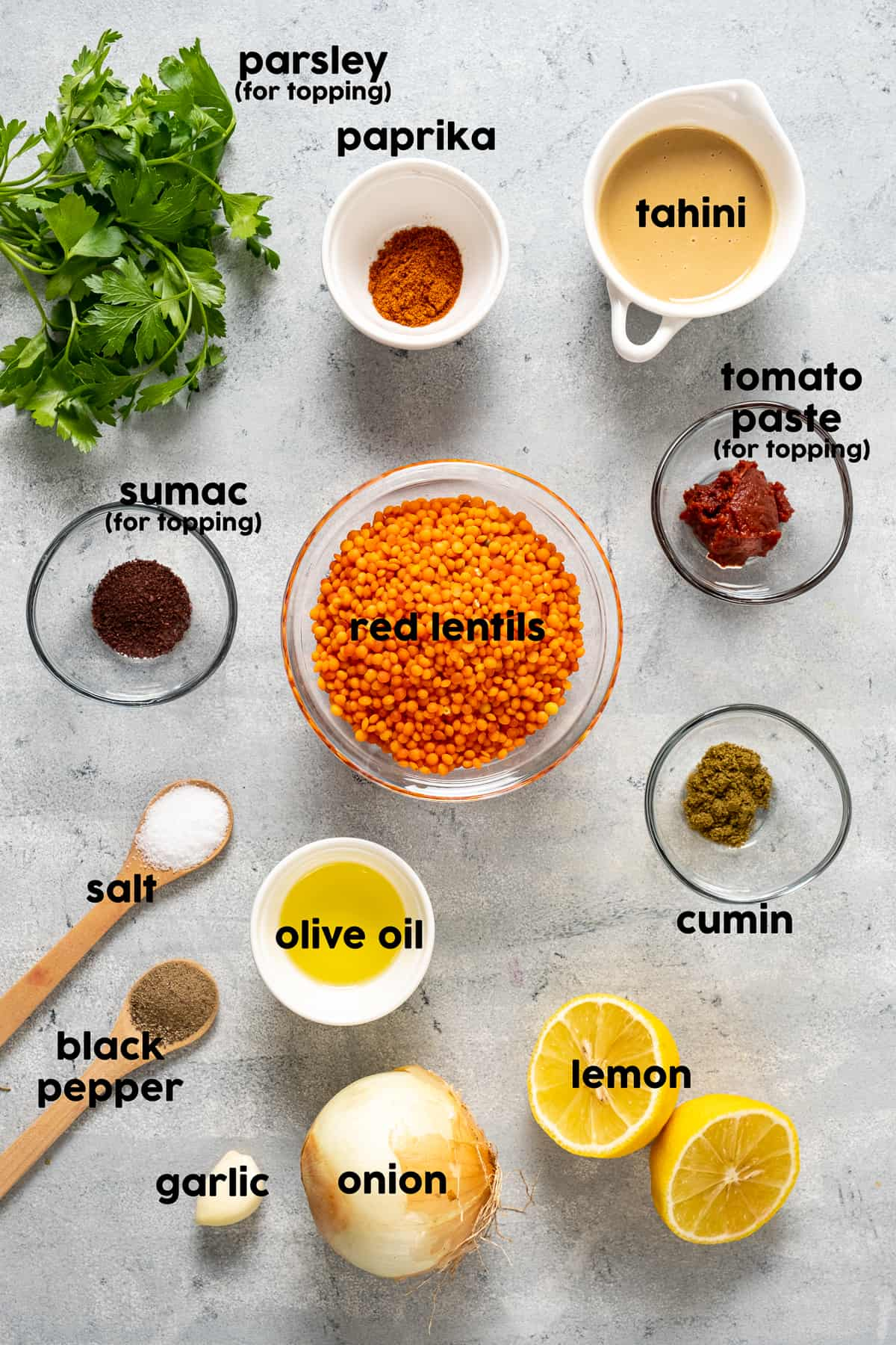 Red lentils, tahini, paprika, sumac, tomato paste, cumin, olive oil in small bowls and halved lemon, onion, garlic, salt and pepper and parsley on the ground.