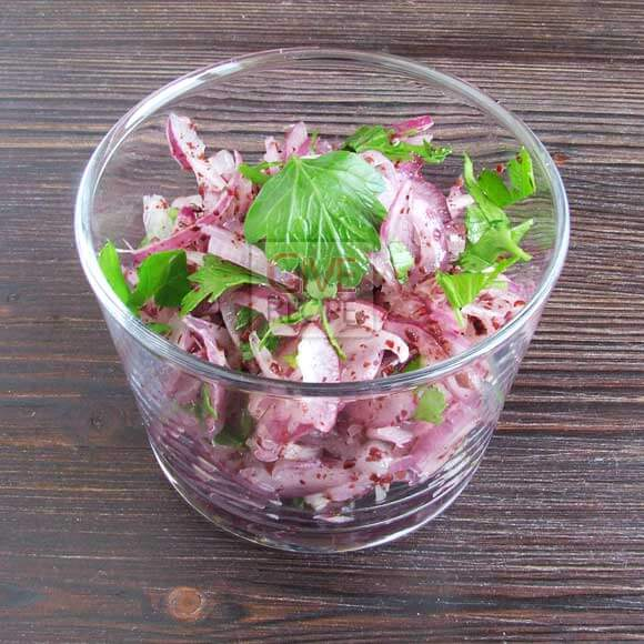 Onion salad with sumac and parsley in a bowl