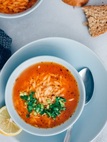 Turkish tomato orzo soup garnished with parsley is served in light blue bowls on a grey background.