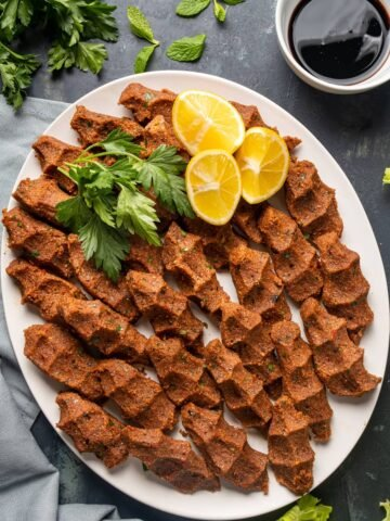 vegan cig kofte on a white oval plate, garnished with lemon wedges and parsley.