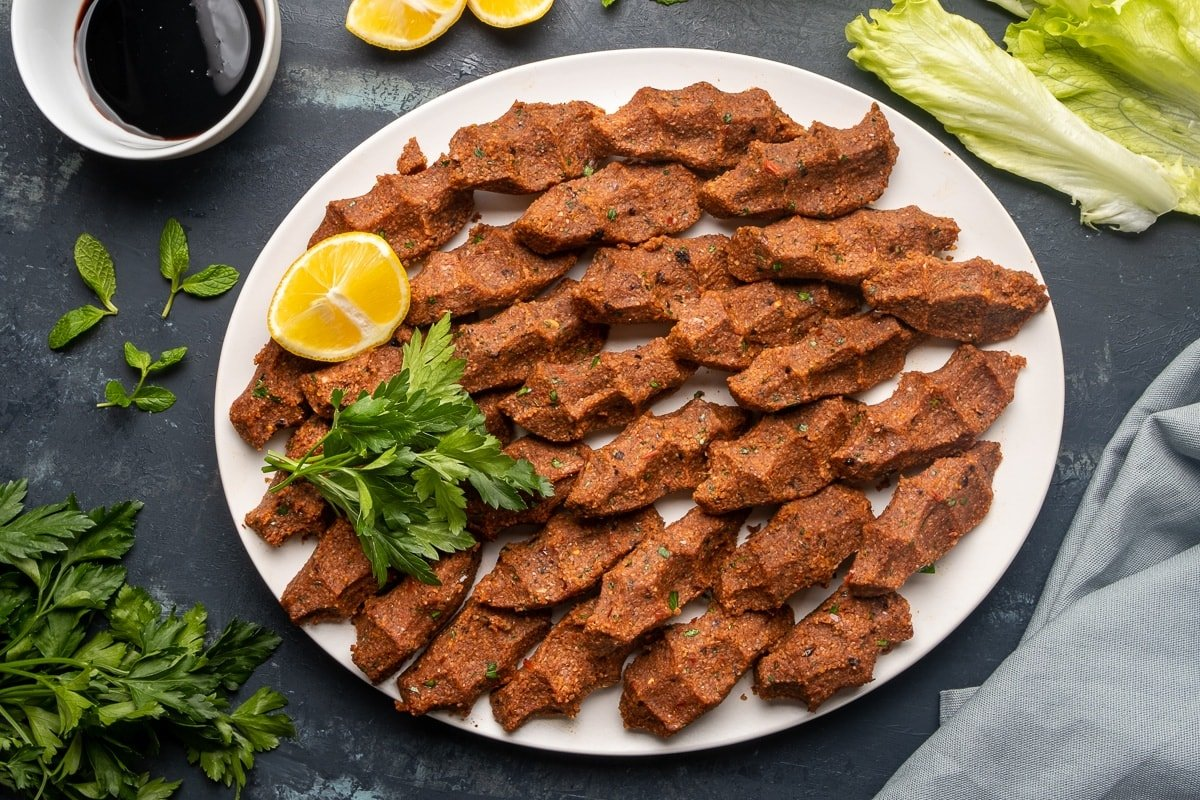 Turkish cigkofte with fine bulgur and spices on a white plate with parsley and lemon wedges and pomegranate molasses and lettuce leaves on the side.