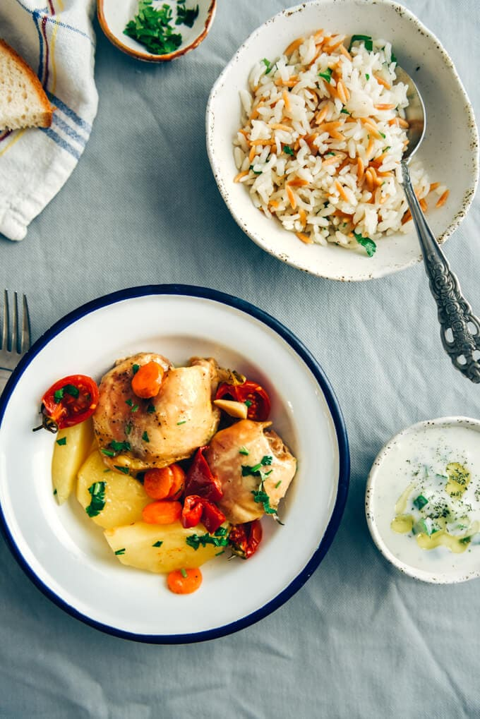 Roast chicken with vegetables in a white bowl accompanied by yogurt dip and rice