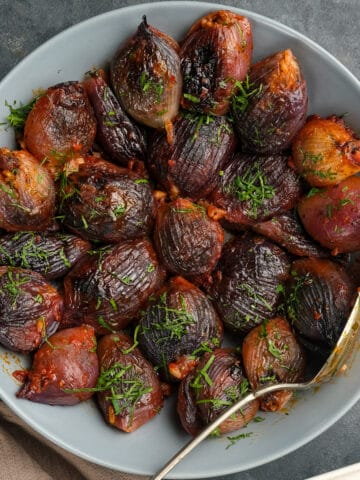 Stuffed purple onions baked in tomato sauce garnished with chopped parsley served in a white bowl with a spoon in it.