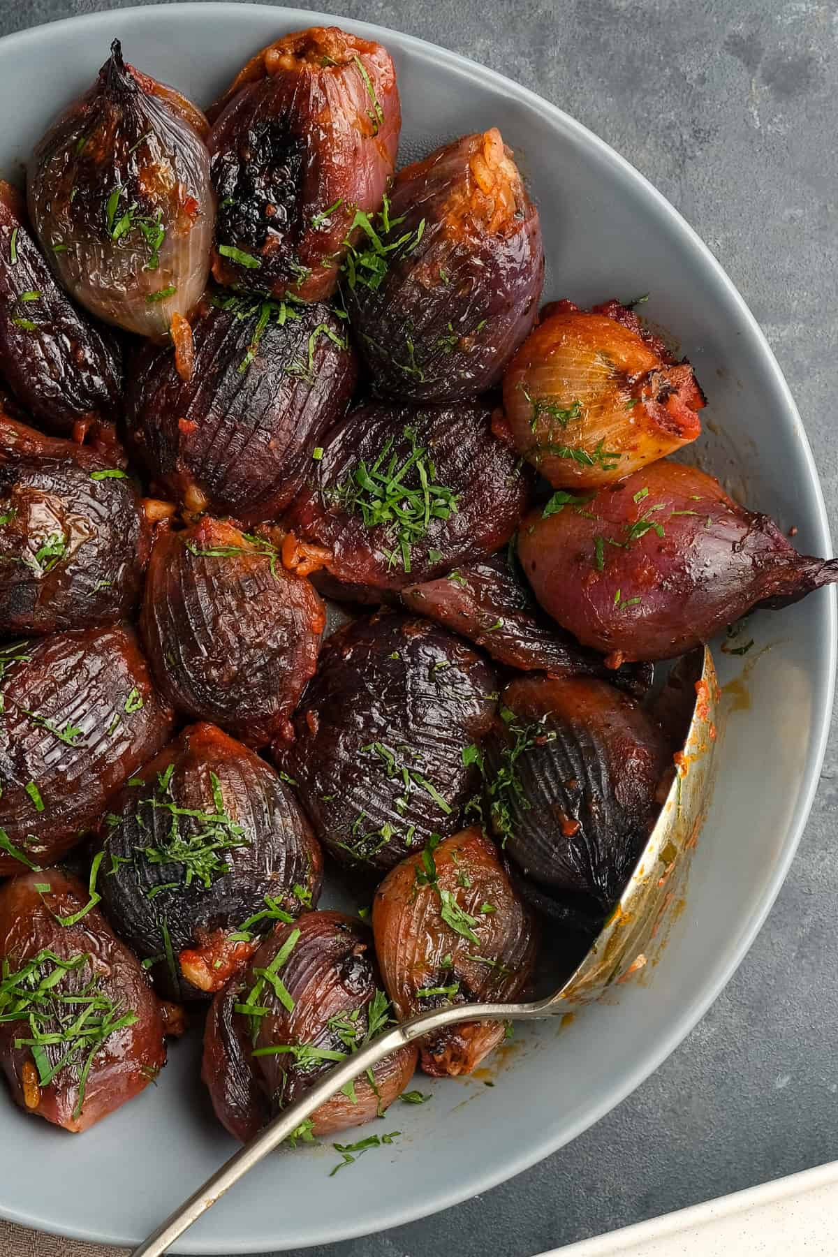 Baked stuffed onions in tomato sauce garnished with shopped parsley in a white dish with a spoon inside it.