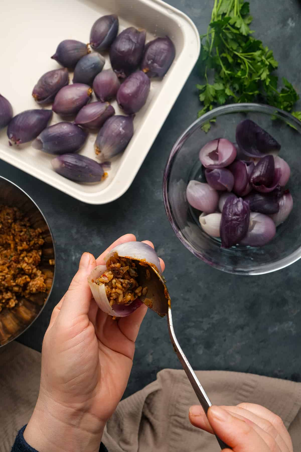 Hands stuffing an onion with ground beef and rice filling with a spoon more stuffed onions in a pan and onion layers in a bowl on the side.