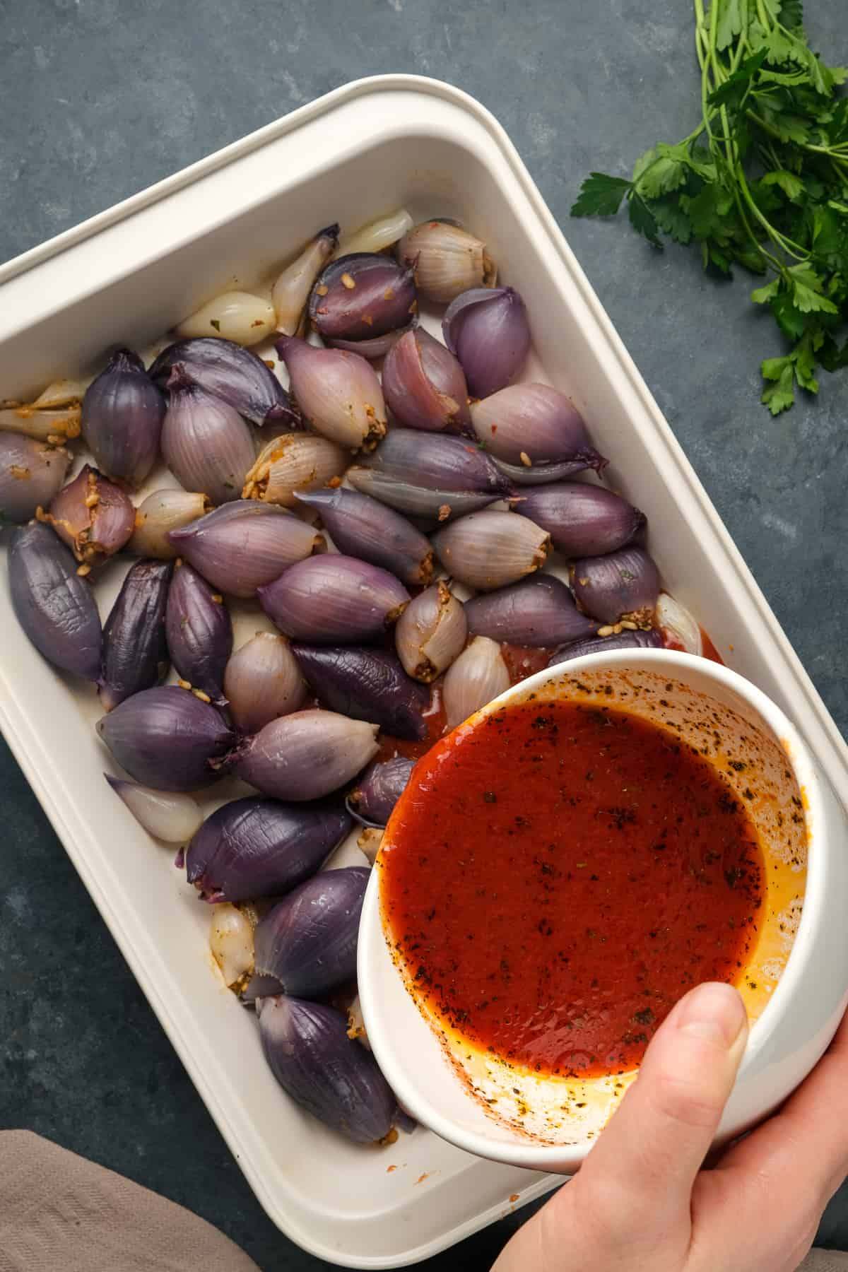 A hand pouring tomato sauce over stuffed purple onions in a baking pan.