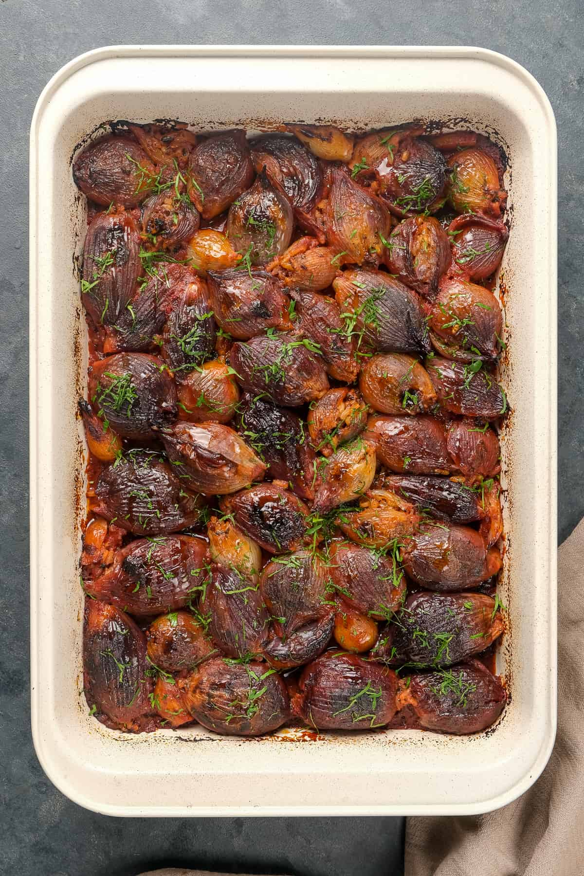 Stuffed and roasted onions with a tomato sauce in a baking pan.